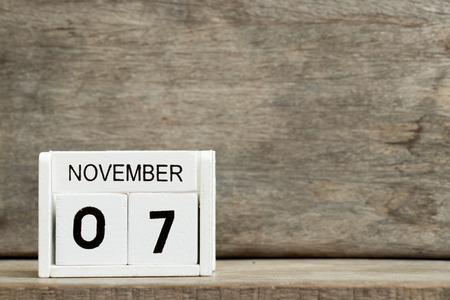 White block calendar present date 7 and month November on wood background