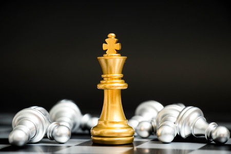 Foto de Gold king in chess game face with the another silver team on black background (Concept for company strategy, business victory or decision) - Imagen libre de derechos