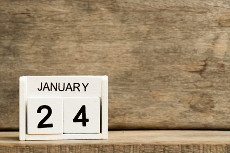 White block calendar present date 24 and month January on wood background