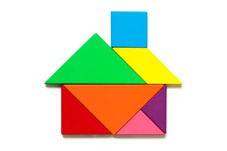 Photo pour Color wood tangram puzzle in home shape on white background - image libre de droit