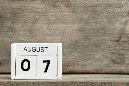 White block calendar present date 7 and month August on wood background