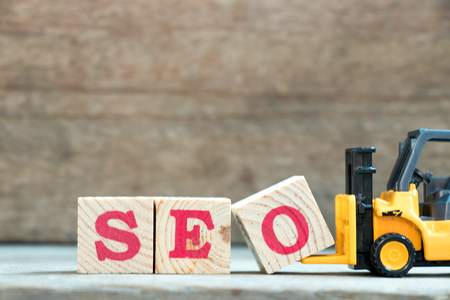 Foto de Yellow toy forklift hold letter block O to complete word SEO (Abbreviation of search engine optimization) on wood background - Imagen libre de derechos