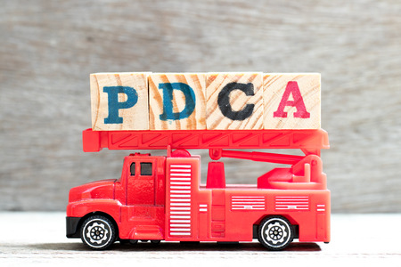 Toy fire ladder truck hold letter block in word PDCA (Plan, Do, Check, Act) on wood background