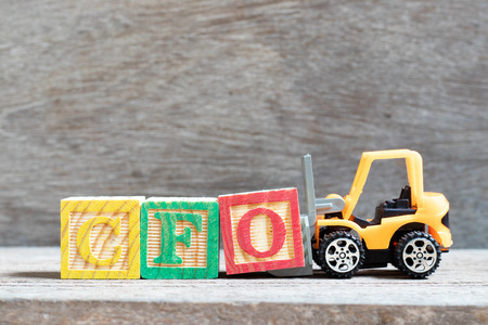 Toy forklift hold letter block O to complete word CFO (Abbreviation of Chief Financial Officer) on wood background