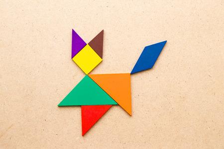 Foto de Color tangram puzzle in cat shape on wood background - Imagen libre de derechos