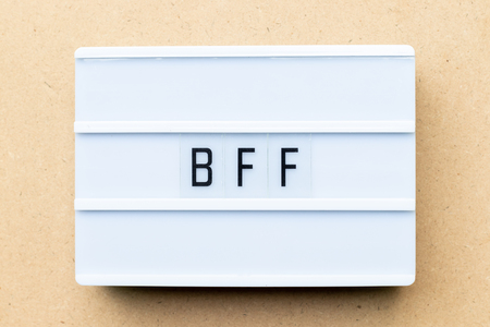 Photo pour White lightbox with word BFF (Abbreviation of best friend forever) on wood background - image libre de droit