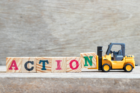 Toy forklift hold letter block n to complete word action on wood background