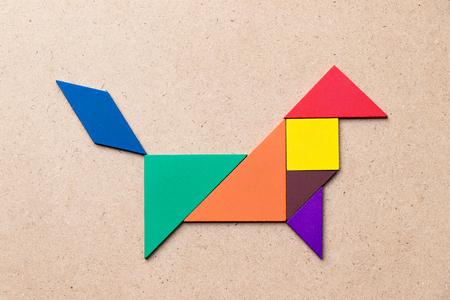 Foto de Color tangram in dog or wolf shape on wood background - Imagen libre de derechos