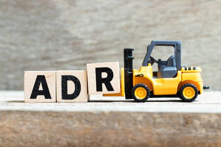 Photo for Toy forklift hold letter block r to complete word ADR (Abbreviation of Adverse drug reaction) on wood background - Royalty Free Image