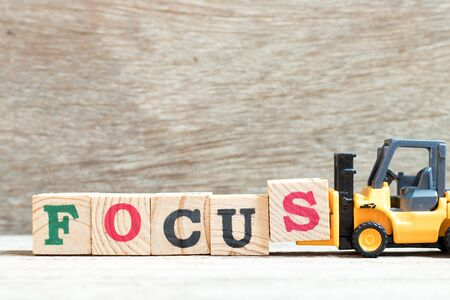 Foto de Toy forklift hold letter block s to complete word focus on wood background - Imagen libre de derechos