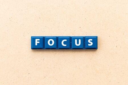 Foto de Tile letter in word focus on wood background - Imagen libre de derechos