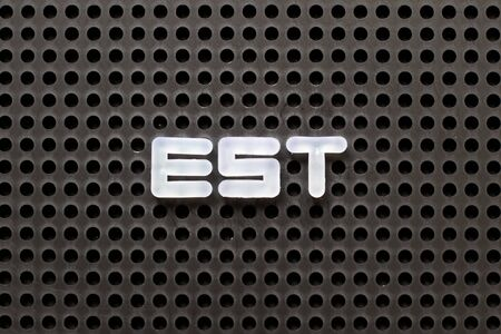 Black color pegboard with white letter in word est