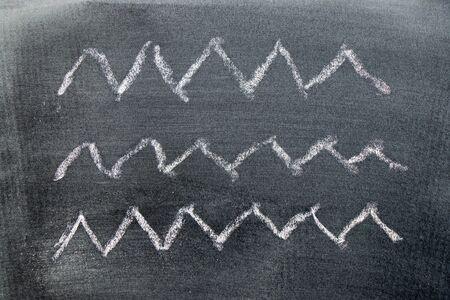 White color chalk hand drawing in zigzag line shape on black board background