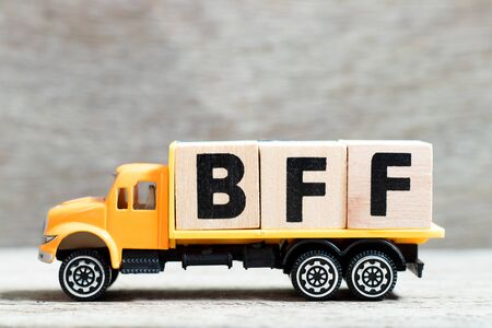 Photo pour Truck hold letter block in word BFF (Abbreviation of best friend forever) on wood background - image libre de droit