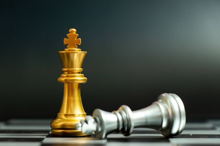 Photo pour Gold king chess piece win over lying down silver king on black background - image libre de droit