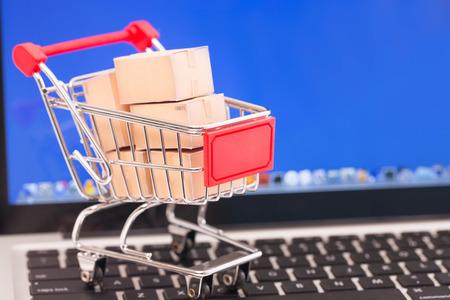 Photo pour Shopping cart with cardboard boxes on laptop. E-commerce concept. - image libre de droit