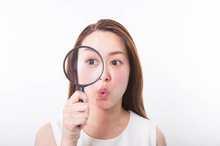 Young woman looking through a magnifying glass on a white background