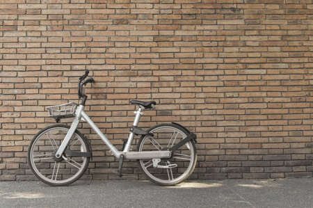 Photo pour Retro bicycle on roadside with vintage brick wall background with copy space. - image libre de droit