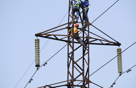 Silhouette electrician work installation of high voltage in high voltage stations safely and systematically over blurred