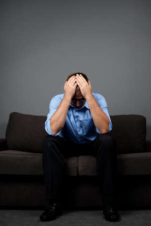 Depressed man sitting on sofa with hands on head
