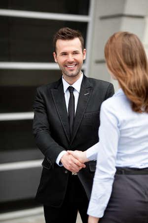 Foto de Mid adult businessman shaking hand with businesswoman. - Imagen libre de derechos