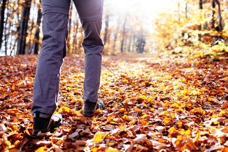 Photo pour Autumn hiking. Close up of female walking uphill with lots of leaves around - image libre de droit