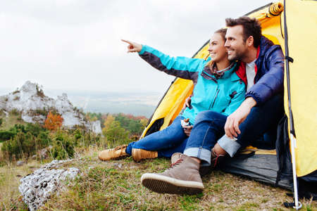 Foto de Couple camping. Young people sitting in tent watching the view - Imagen libre de derechos