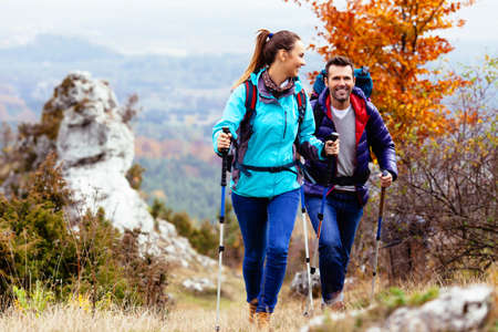 Photo pour Woman and man hiking in mountains with backpacks - image libre de droit