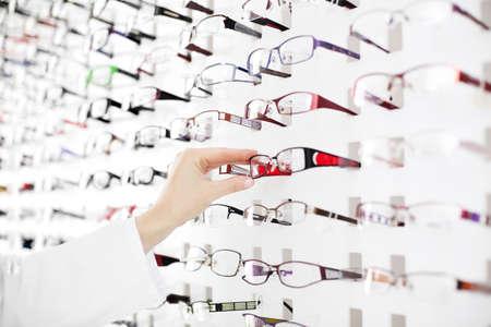 Photo pour Optician suggest glasses. Closeup showing many eyeglasses in background. - image libre de droit