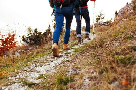 Foto de Couple hiking in mountains, walking uphill - Imagen libre de derechos