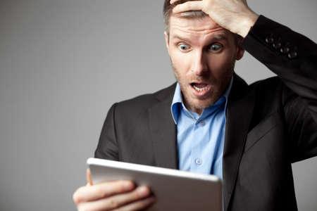 Foto de Shocked businessman with digital tablet - Imagen libre de derechos