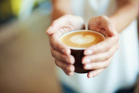 Foto de Closeup of Female holding coffee with heart symbol - Imagen libre de derechos