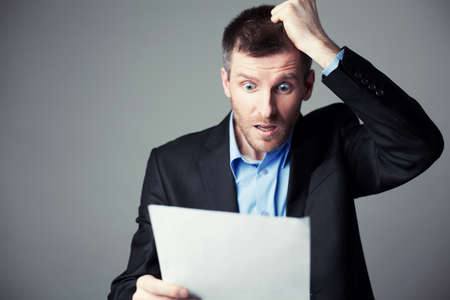 Photo pour terrified businessman reads contract and pulls his hair from head - image libre de droit