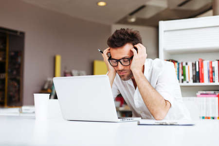 Photo for Tired student or businessman working with laptop in the office - Royalty Free Image