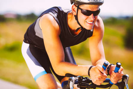 Photo pour Happy triathlete cycling on a bicycle - image libre de droit