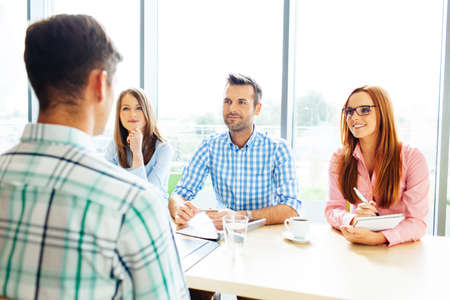 Photo for Recruitment. Three corporate people Interview young man - Royalty Free Image