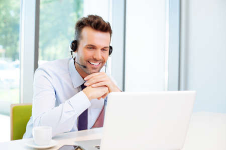 Photo for Happy consultant with headset looking at laptop - Royalty Free Image