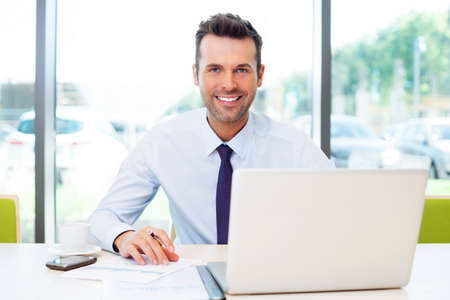 Photo pour Happy businessman working at the office on laptop. - image libre de droit