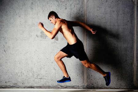 Photo pour Photo of a running muscular sportsman on a concrete background - image libre de droit