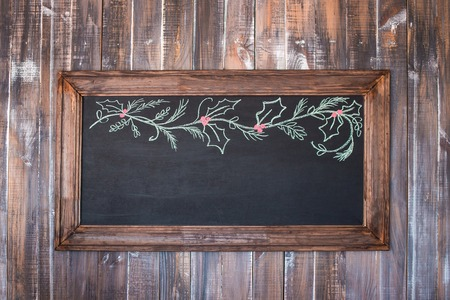 Front view of a blank blackboard over a weathered wooden surface, blackboard
