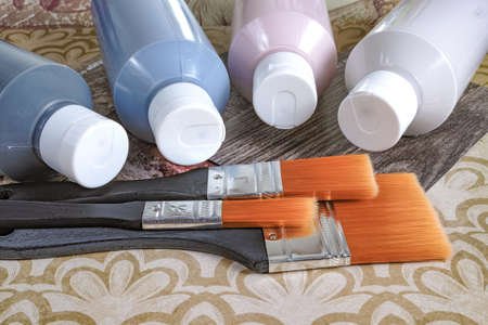 Four bottles with acrylic paint and brushes on background with ornament, for hobby, drawing, home decoration, renovation