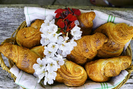 Fresh french croissants in a basket from bakery on wooden background