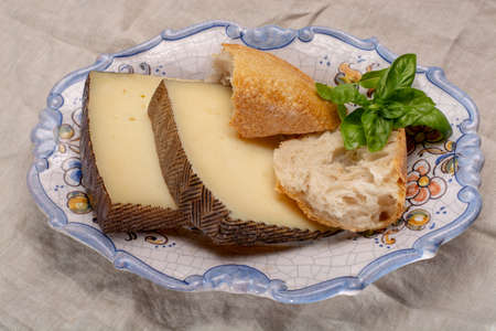 Two pieces of Manchego, queso manchego, cheese made in La Mancha region of Spain from the milk of sheep of the manchega breed served on traditional spanish board with bread