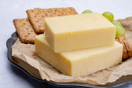 Foto de Block of aged cheddar cheese, the most popular type of cheese in United Kingdom and USA, natural cheese made from cow milk - Imagen libre de derechos