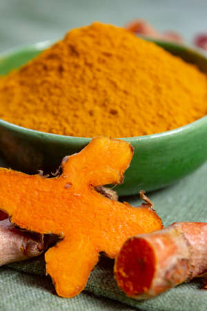 Fresh turmeric or curcuma root and dried powder, wildly used in Asia and India as spice, food ingredient and for medicinal purposes  close up