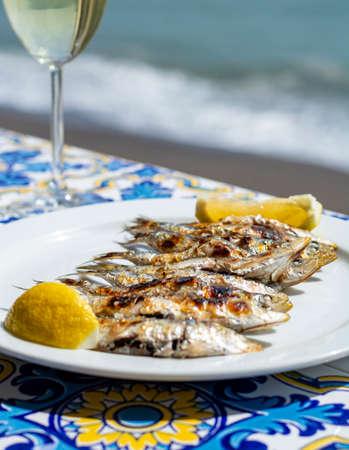 Foto de Sardines espeto, Malaga style fish on stick barbecue prepared on olive tree firewoods on beach served with white wine - Imagen libre de derechos