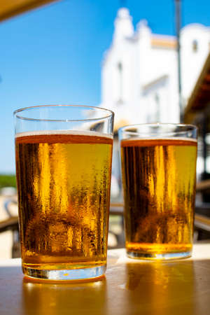 Photo pour Cold amber color light spanish beer served in glass in outdoor cafe in town on sand, El Rocio in Andalusia, Spain close up - image libre de droit