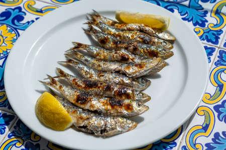 Foto de Sardines espeto, Malaga style fish on stick barbecue prepared on olive tree firewoods on beach - Imagen libre de derechos