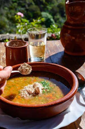 Homemade vegetables soup served on outdoor terrace with Canarian gofio flour based on local recipe of Masca village, Tenerife, Spain