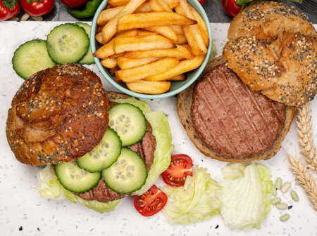 Photo pour Making tasty vegetarian vegan lunch with hamburger made from plant based soya beans burger, organic bun with seeds and fresh garden vegetables and french fried potatoes - image libre de droit